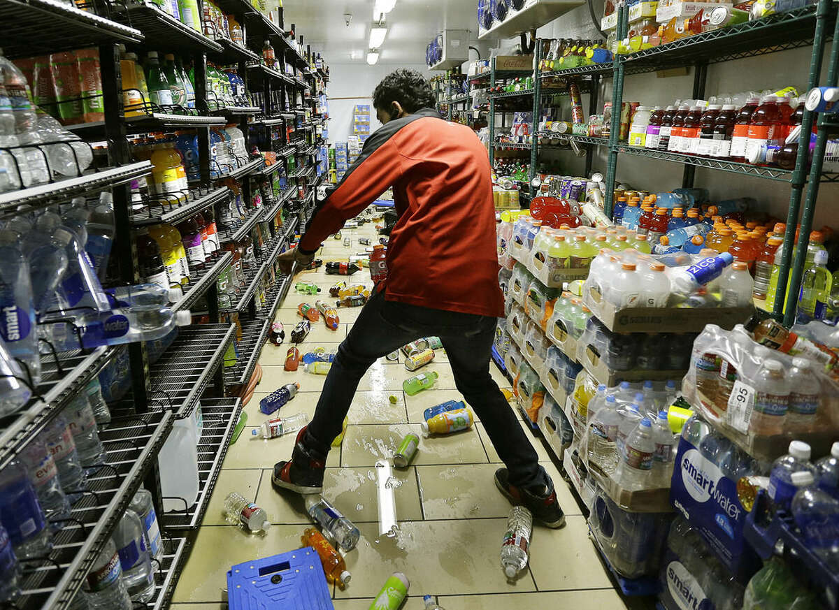 Gurbeer Singh cleans up merchandise which fell due to an earthquake at a 7-Eleven store Sunday, Aug. 24, 2014, in American Canyon, Calif. Officials say an earthquake with a preliminary magnitude of 6.0 has been reported in California's northern San Francisco Bay area. (AP Photo/Ben Margot)