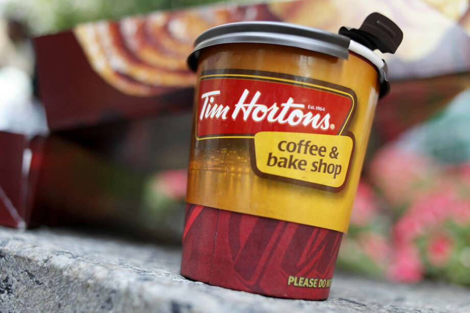FILE - In this Wednesday, July 22, 2009, file photo, a Tim Hortons coffee cup is seen in New York. The Canadian doughnut chain moved into 12 former Dunkin Donut locations earlier in the month, bringing new blood to the doughnut war in America's most competitive market. (AP Photo/Seth Wenig, File)