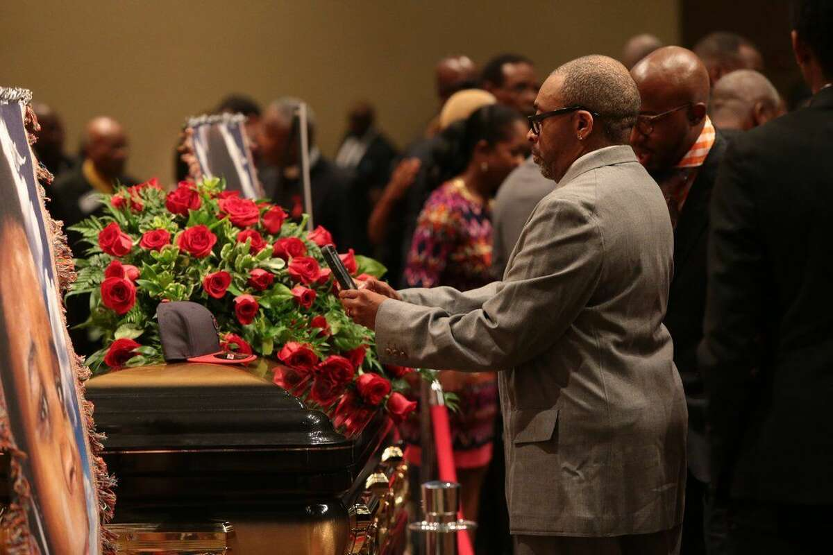 Director Spike Lee takes a picture of a black St. Louis Cardinals baseball cap on top of Michael Brown's casket on Monday, Aug. 25, 2014, during the funeral services at Friendly Temple Missionary Baptist Church in St. Louis. Michael Brown, 18, was shot and killed by a Ferguson police officer on Aug. 9, 2014. (AP Photo/St. Louis Post Dispatch, Robert Cohen, Pool)