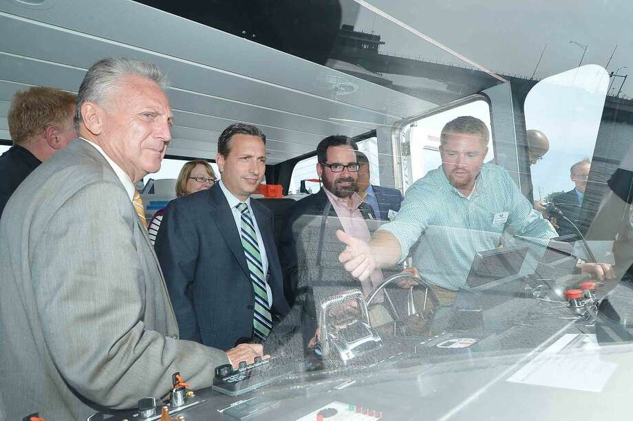 Hour Photo/Alex von Kleydorff Department Energy of and Environmental Protection Commissioner, Rob Klee sits at the helm of the Maritime Aquarium's R/V Spirit of the Sound, while Director of Vessel Operations and Lead Captain Travis Mingo shows State Sen. Bob Duff and Norwalk Mayor Harry Rilling the Aquarium's Hybrid Electric research vessel