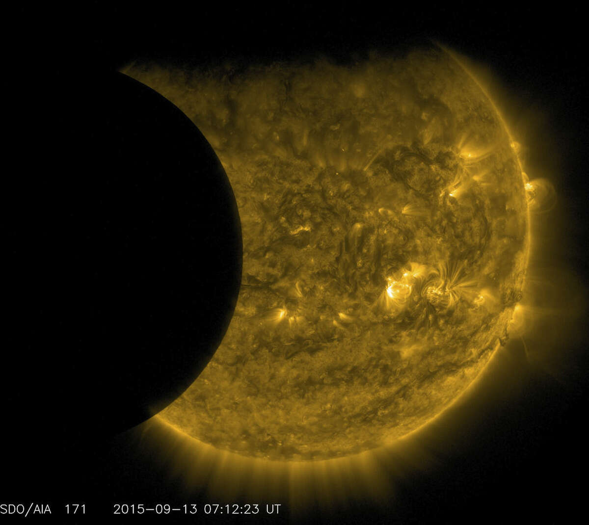 This Sept. 13, 2015 image provided by NASA shows the moon, left, and the Earth, top, transiting the sun together, seen from the Solar Dynamics Observatory. The edge of Earth appears fuzzy because the atmosphere blocks different amounts of light at different altitudes. This image was taken in extreme ultraviolet wavelengths, invisible to human eyes, but here colorized in gold. A total lunar eclipse will share the stage with a so-called supermoon Sunday evening, Sept. 27, 2015 as seen from the United States. That combination hasn't been seen since 1982 and won't happen again until 2033. (NASA/SDO via AP)