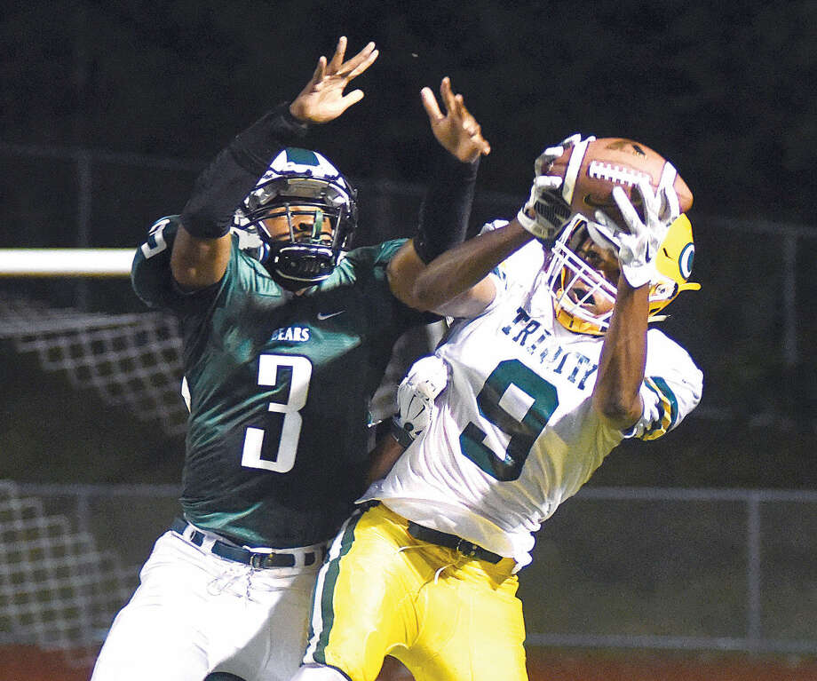 Hour photo/John Nash - Trinity Catholic's Izaiah Sanders, right, hauls in a 10-yard scoring pass against the defense of Norwalk's Lester Harris during the first quarter of Friday's FCIAC football game at Testa Field in Norwalk. Trinity Catholic eked out a controversial 22-20 win over the host Bears.
