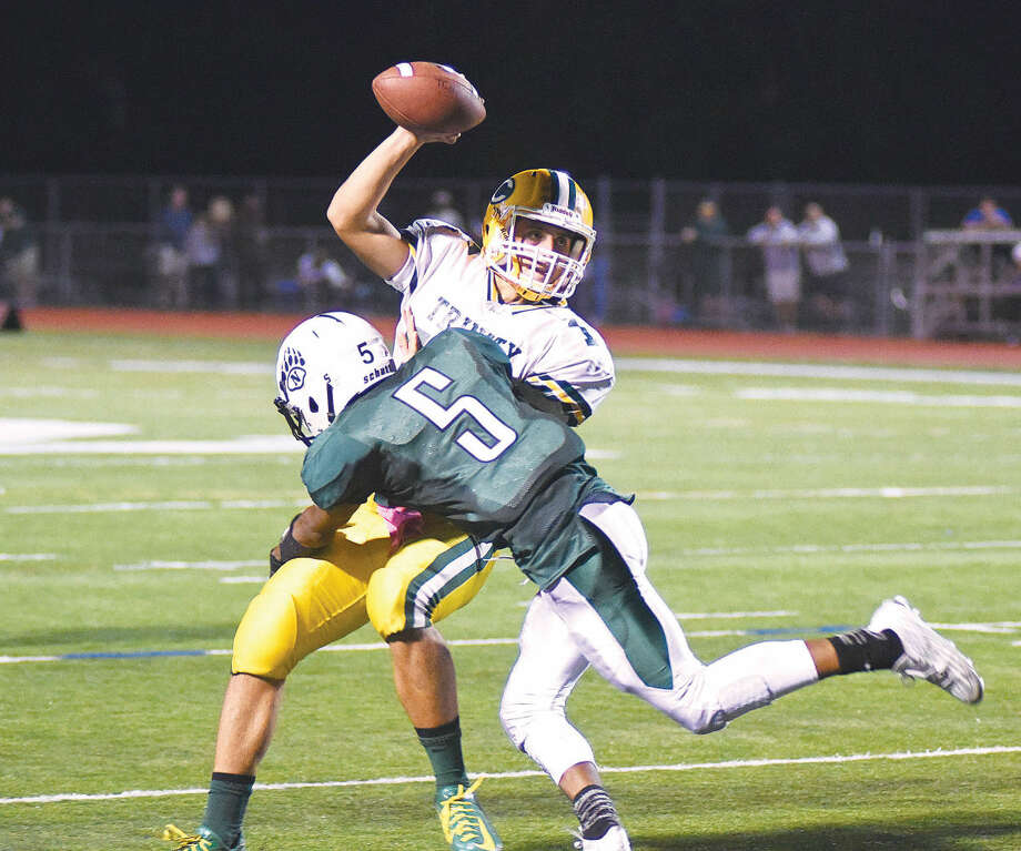 Hour photo/John Nash - Norwalk's Amyr Rivera (5) looks to bring down Trinity Catholic quarterback Anthony Lombardi during the first half of Friday night's FCIAC football game in Norwalk.