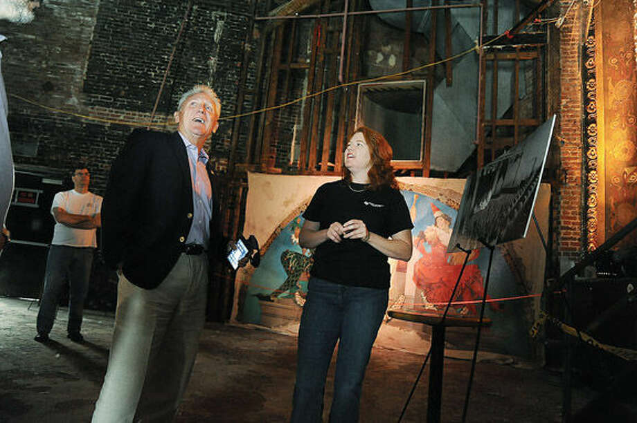 Wall Street theater president Suzanne Cahill shows Norwalk Mayor Harry Rilling the progress of the performance area of the theater Sunday at the street festival celebrating the theater's 100th anniversary. Hour photo/Matthew Vinci
