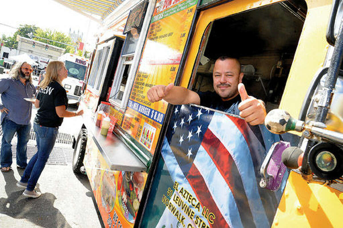 Juan Martinez owner of the food truck Tacos El Azteca was among the many food trucks Sunday at the street festival celebrating the 100th anniversary of the Wall Street Theater. Hour photo/Matthew Vinci