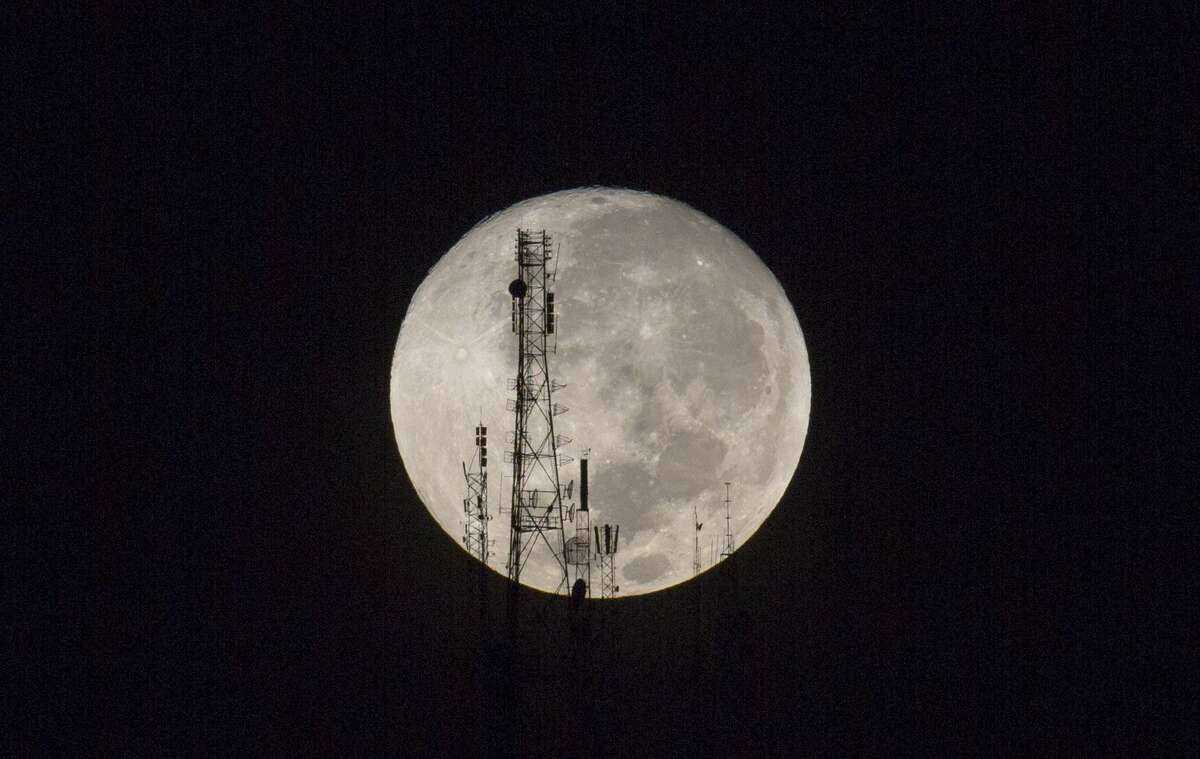 A full moon silhouettes television and radio antennas on Boutilier Mountain, in Port-au-Prince, Haiti, early Sunday Sept. 27, 2015. The full moon was seen prior to a phenomenon called a