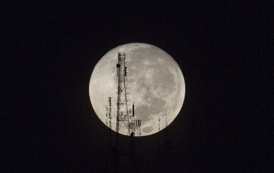 """A full moon silhouettes television and radio antennas on Boutilier Mountain, in Port-au-Prince, Haiti, early Sunday Sept. 27, 2015. The full moon was seen prior to a phenomenon called a """"Super Moon"""" eclipse that will occur Sunday night. (AP Photo/Dieu Nalio Chery)"""