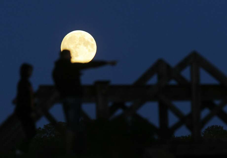 "People watch a perigee moon, also known as a super moon, rises in Mir, Belarus, 95 kilometers (60 miles) west of capital Minsk, Belarus, late Sunday, Sept. 27, 2015. The full moon was seen prior to a phenomenon called a ""Super Moon"" eclipse that will occur on Monday, Sept. 28. (AP Photo/Sergei Grits)"