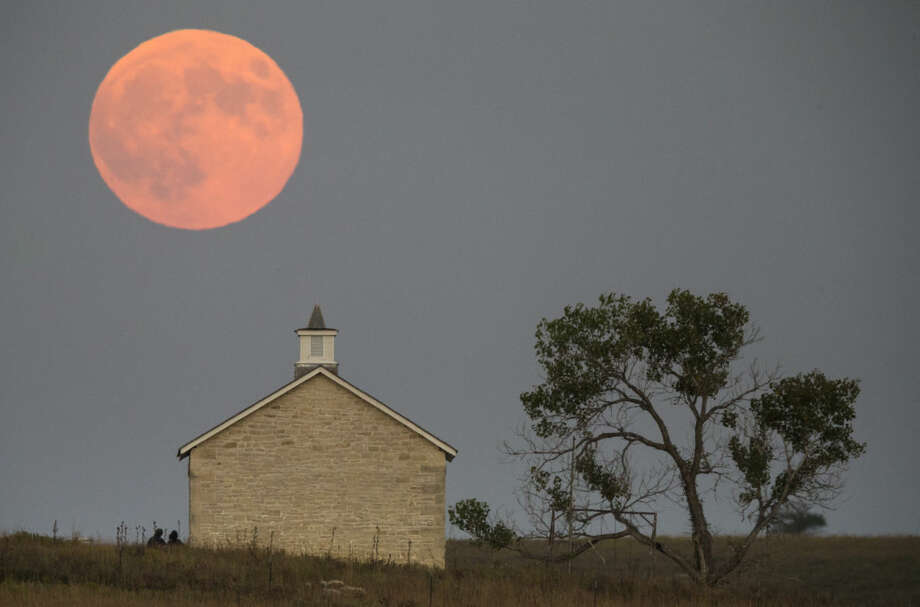 A super moon rises over the Lower Fox Creek School near Strong City, Kan., Sunday, Sept. 27, 2015. It was the first time Sunday since 1982 that a total lunar eclipse was combined with a supermoon. (Travis Heying/The Wichita Eagle via AP) LOCAL TELEVISION OUT; MAGS OUT; LOCAL RADIO OUT; LOCAL INTERNET OUT; MANDATORY CREDIT