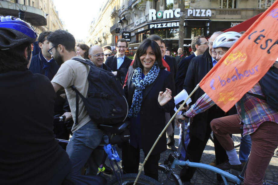 "Paris Mayor, Anne Hidalgo, center, arrives to launch the ""day without cars"", on the Champs Elysees, in Paris, Sunday, Sept. 27, 2015. Pretty but noisy Paris, its gracious Old World buildings blackened by exhaust fumes, is going car-less for a day. Paris Mayor Anne Hidalgo presided over Sunday's ""day without cars,"" two months before the city hosts the global summit on climate change. (AP Photo/Thibault Camus)"