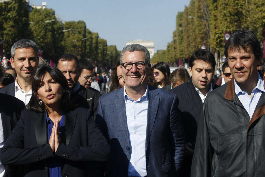 """From left, Paris Mayor, Anne Hidalgo, Brussels mayor Yvan Mayeur, and Sao Paulo, Brazil, Mayor Fernando Haddad, walk on the Champs Elysees during the """"day without cars"""", in Paris, France, Sunday, Sept. 27, 2015. Pretty but noisy Paris, its gracious Old World buildings blackened by exhaust fumes, is going car-less for a day. Paris Mayor Anne Hidalgo presided over Sunday's """"day without cars,"""" two months before the city hosts the global summit on climate change. (AP Photo/Thibault Camus)"""