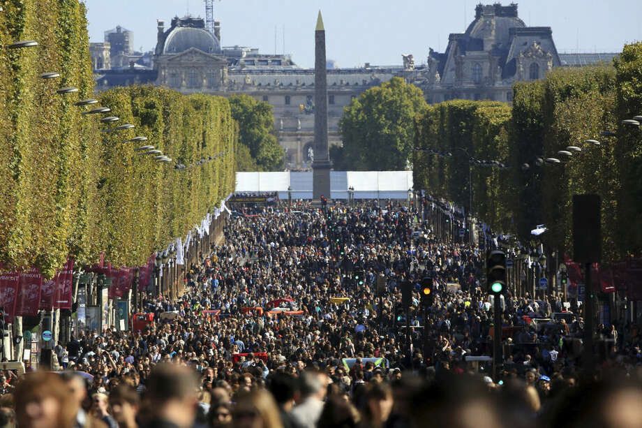"""People walk on the Champs Elysees during the """"day without cars"""", in Paris, France, Sunday, Sept. 27, 2015. Pretty but noisy Paris, its gracious Old World buildings blackened by exhaust fumes, is going car-less for a day. Paris Mayor Anne Hidalgo presided over Sunday's """"day without cars,"""" two months before the city hosts the global summit on climate change. (AP Photo/Thibault Camus)"""
