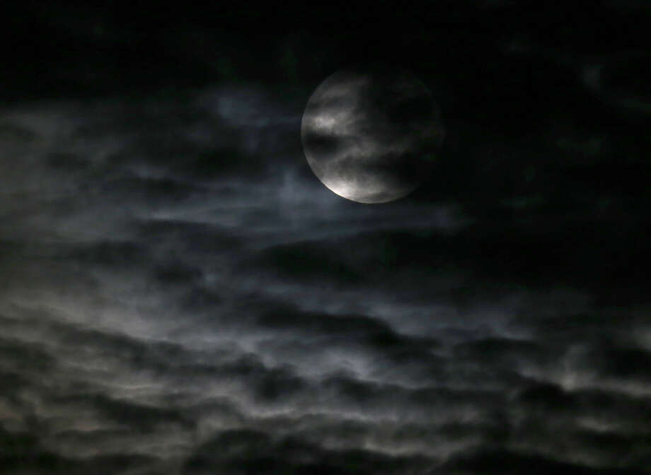 Clouds obscure the so-called supermoon before a lunar eclipse Sunday, Sept. 27, 2015, in Chicago. It's the first time the events have made a twin appearance since 1982, and they won't again until 2033. (AP Photo/Charles Rex Arbogast)
