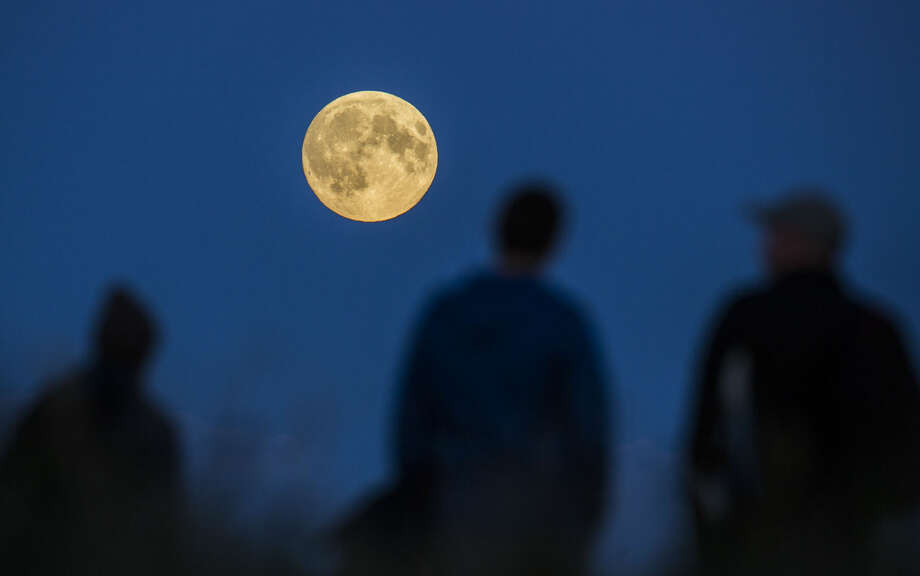 """People watch a full moon rising in Berlin, Germany, Sunday, Sept. 27, 2015. The full moon was seen prior to a phenomenon called a """"Super Moon"""" eclipse that will occur during moonset on Monday morning, Sept. 28. (AP Photo/Gero Breloer)"""