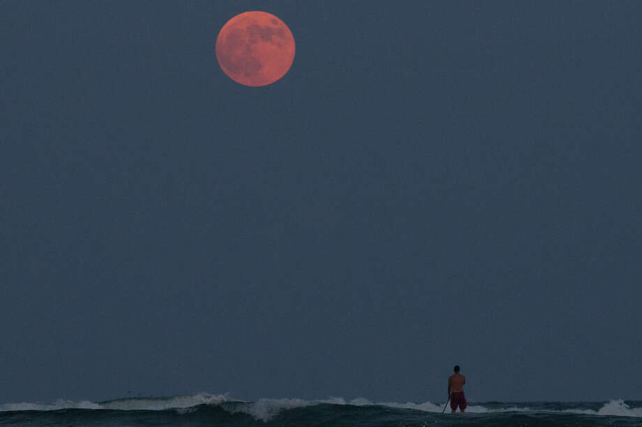 A paddle border looks out at the so-called supermoon from the water off Padre Island Balli park in Corpus Christi, Texas, Sunday, Sept. 27, 2015. (Courtney Sacco/Corpus Christi Caller-Times via AP) MANDATORY CREDIT; MAGS OUT; TV OUT