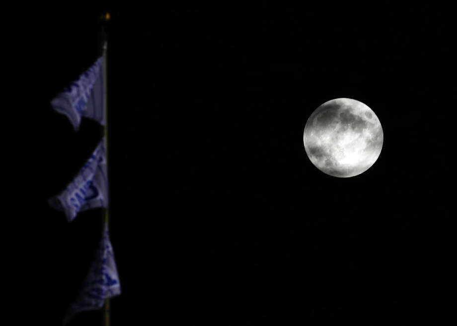 A so-called supermoon rises in the sky before a total lunar eclipse at Wrigley Field, Sunday, Sept. 27, 2015, in Chicago. It was the first time the events have made a twin appearance since 1982, and they won't again until 2033. (AP Photo/Nam Y. Huh)