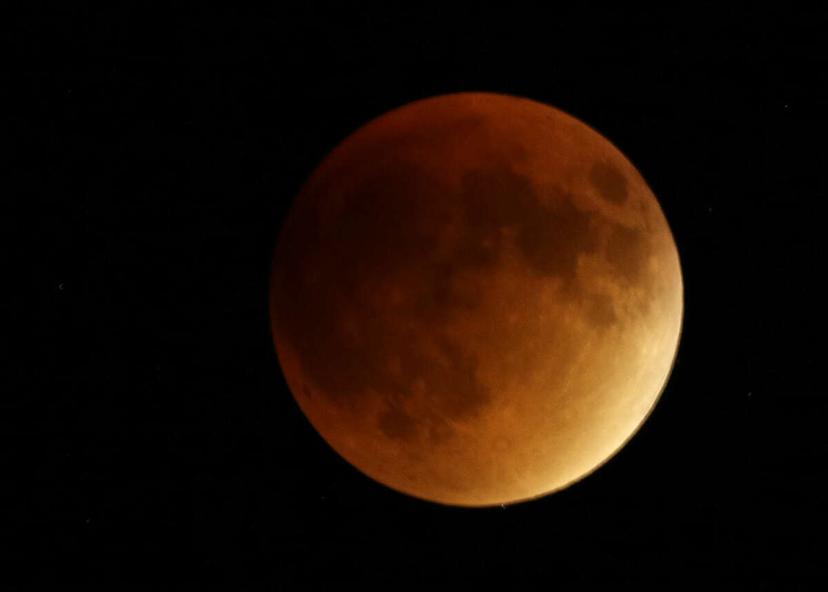 Earth's shadow obscures the view of a so-called supermoon during a total lunar eclipse Sunday, Sept. 27, 2015, near Lecompton, Kan. It was the first time Sunday that the events have made a twin appearance since 1982, and they won't again until 2033. (AP Photo/Orlin Wagner)