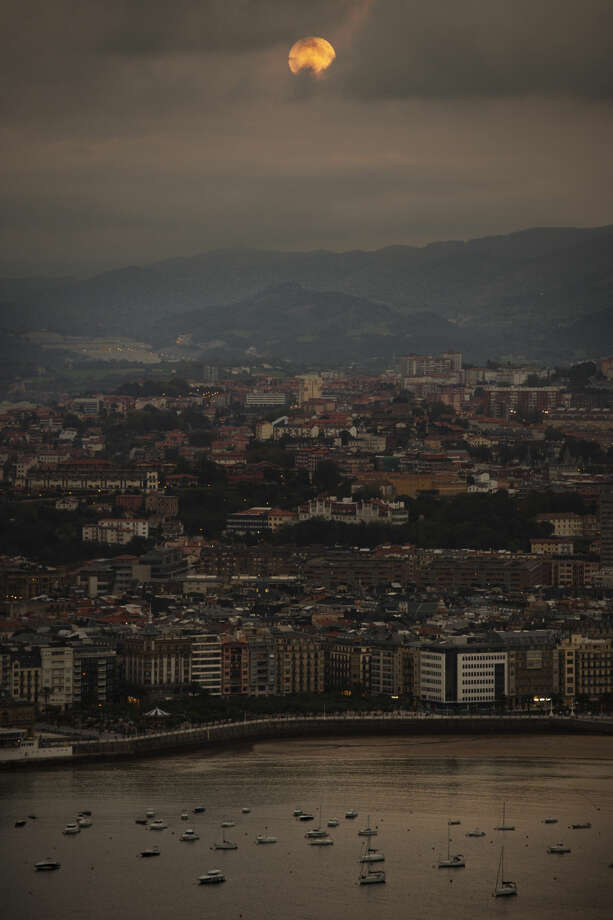 """A perigee moon also known as a supermoon, rises in the sky above the La Concha Beach, in San Sebastian, northern Spain, Sunday Sept. 27, 2015. The phenomenon, which scientists call a """"perigee moon,"""" occurs when the moon is near the horizon and appears larger and brighter than other full moons. (AP Photo/Alvaro Barrientos)"""