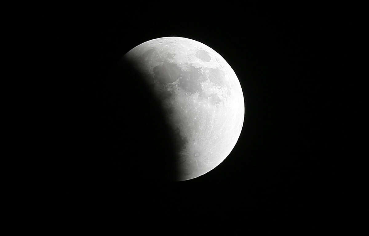 The Earth's shadow starts to obscure the view of the so-called supermoon total lunar eclipse in Miami Gardens, Fla., Sunday, Sept. 27, 2015. It was the first time Sunday that the events have made a twin appearance since 1982, and they won't again until 2033. (AP Photo/Wilfredo Lee)