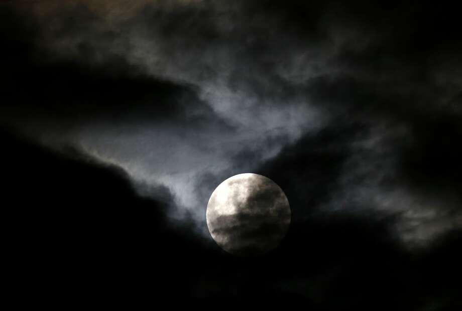 Clouds brake long enough to reveal the so-called supermoon before a lunar eclipse Sunday, Sept. 27, 2015, in Chicago. It's the first time the events have made a twin appearance since 1982, and they won't again until 2033. (AP Photo/Charles Rex Arbogast)