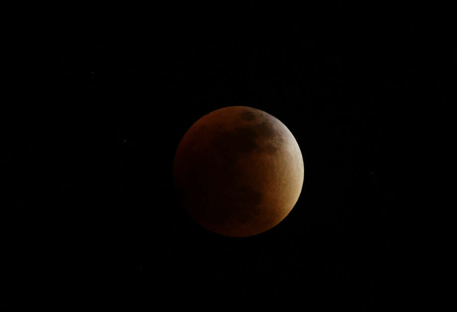 Earth's shadow begins to obscure the view of a so-called supermoon during a total lunar eclipse in Panama City, Sunday, Sept. 27, 2015. (AP Photo/Arnulfo Franco)
