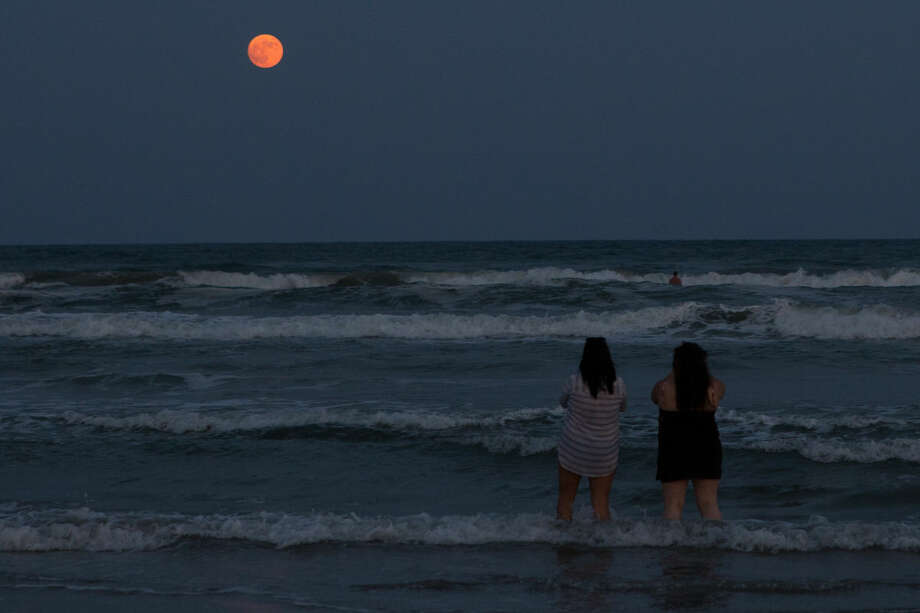 Beach goers take photos of the so-called supermoon from the water off Padre Island Balli park in Corpus Christi, Texas, Sunday, Sept. 27, 2015. (Courtney Sacco/Corpus Christi Caller-Times via AP) MANDATORY CREDIT; MAGS OUT; TV OUT