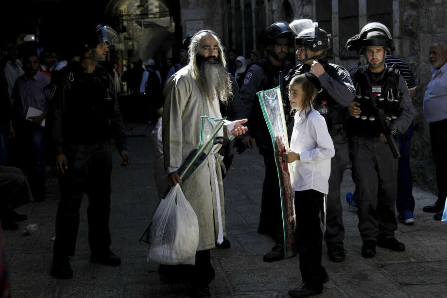 Israeli border police stands by ultra-Orthodox Jews during confrontations in the Old City of Jerusalem, Monday, Sept. 28, 2015. Palestinians clashed with Israeli riot police after barricading themselves in a mosque at Jerusalem's most sensitive holy site, throwing firebombs and rocks at officers outside during a major Jewish holiday on Monday. The hilltop compound in Jerusalem's Old City is a frequent flashpoint and its fate is a core issue at the heart of the Israeli-Palestinian conflict. (AP Photo/Mahmoud Illean)