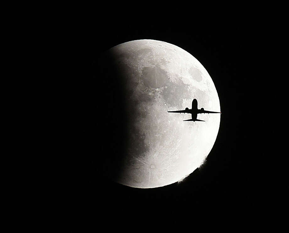 A plane flies in front of the so-called supermoon during a lunar eclipse Sunday, Sept 27, 2015 in Geneva, Ill. It was the first time Sunday that the events have made a twin appearance since 1982, and they won't again until 2033 (Jeff Knox/Daily Herald via AP) MANDATORY CREDIT; MAGS OUT