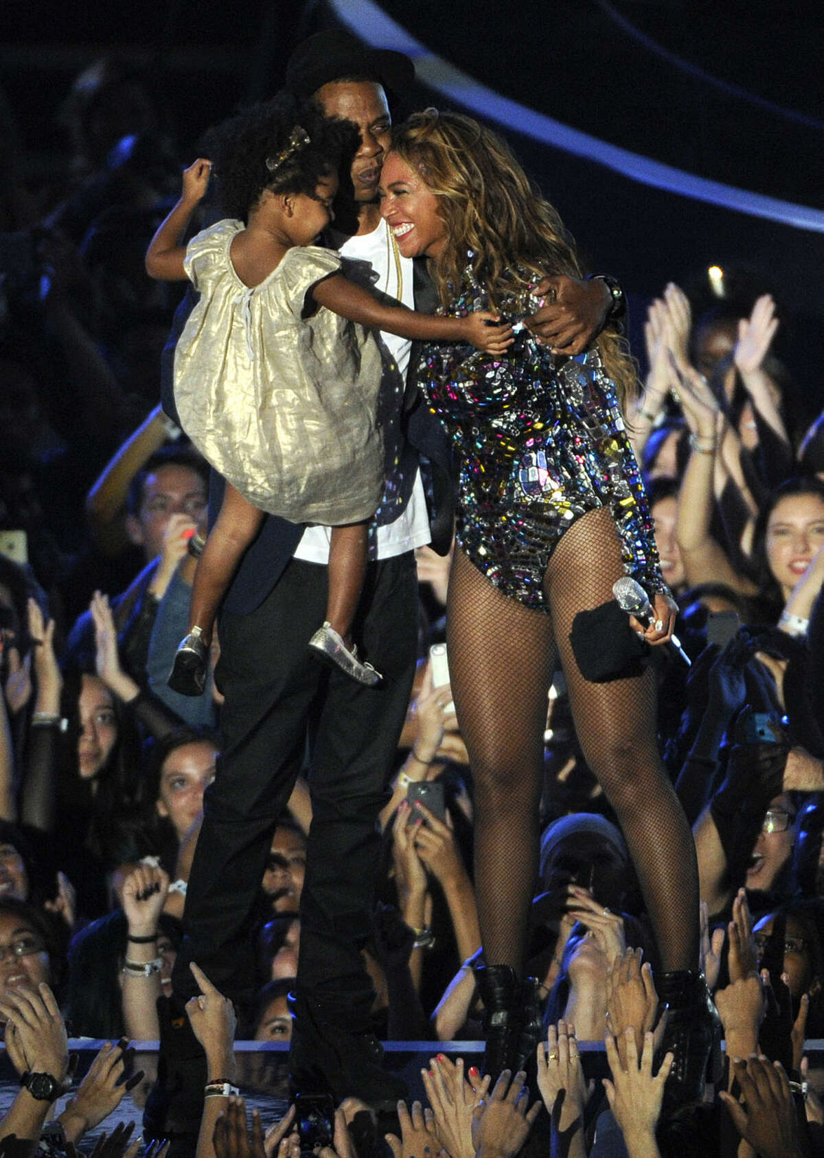 Beyonce smiles on stage with Jay Z and their daughter Blue Ivy as she accepts the Video Vanguard Award at the MTV Video Music Awards at The Forum on Sunday, Aug. 24, 2014, in Inglewood, Calif. (Photo by Chris Pizzello/Invision/AP)