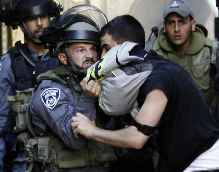An Israeli border policeman grabs a Palestinian man during confrontations in the Old City of Jerusalem, Monday, Sept. 28, 2015. Palestinians clashed with Israeli riot police after barricading themselves in a mosque at Jerusalem's most sensitive holy site, throwing firebombs and rocks at officers outside during a major Jewish holiday on Monday. The hilltop compound in Jerusalem's Old City is a frequent flashpoint and its fate is a core issue at the heart of the Israeli-Palestinian conflict. (AP Photo/Mahmoud Illean)