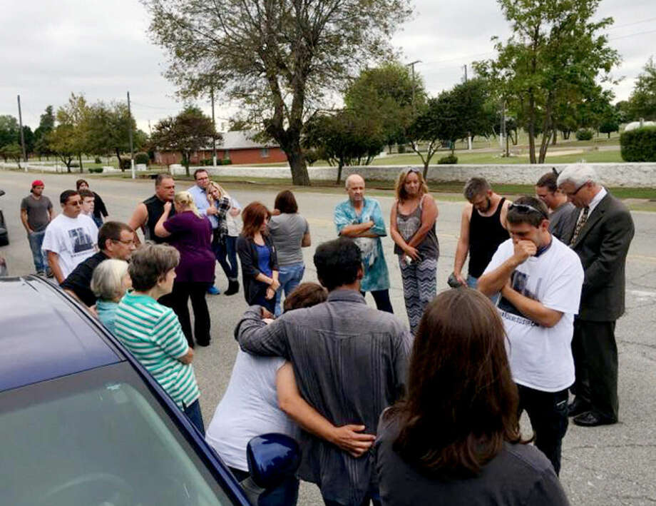 Family members of Richard Glossip and others opposed to Glossip's execution bow their heads outside the Oklahoma State Penitentiary in McAlester, Okla., on Wednesday, Sept. 30, 2015, shortly after learning Glossip's appeal had been denied by the U.S. Supreme Court. Gov. Mary Fallin has granted a last-minute stay saying the state needed to determine whether its use of a new drug, potassium acetate, was in compliance. (David Dishman/McAlester News Capital via AP)