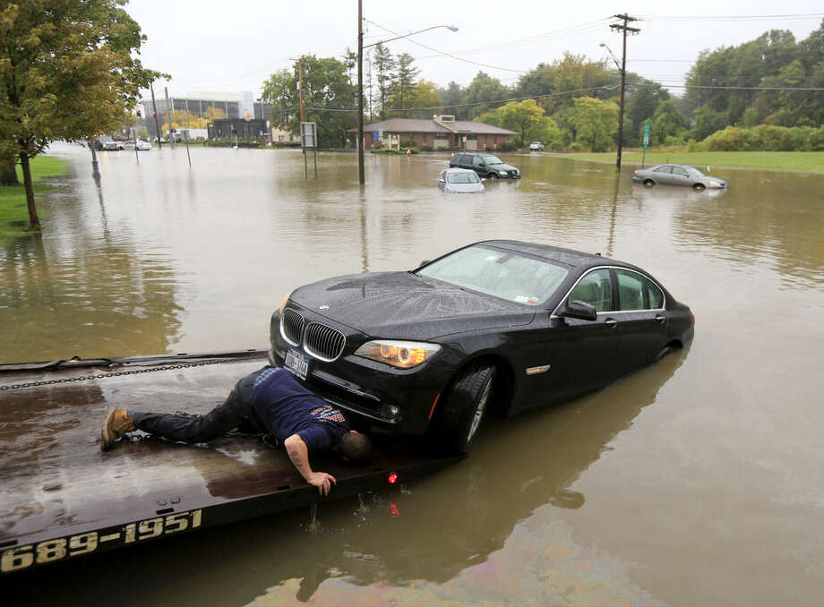 A worker prepares to tow a stranded vehicle from a flooded road on Wednesday, Sept. 30, 2015, in Guilderland, N.Y. The National Weather Service has issued flood watches for much of the eastern half of upstate New York as a storm dumps more than two inches of rain across the region. (AP Photo/Mike Groll)
