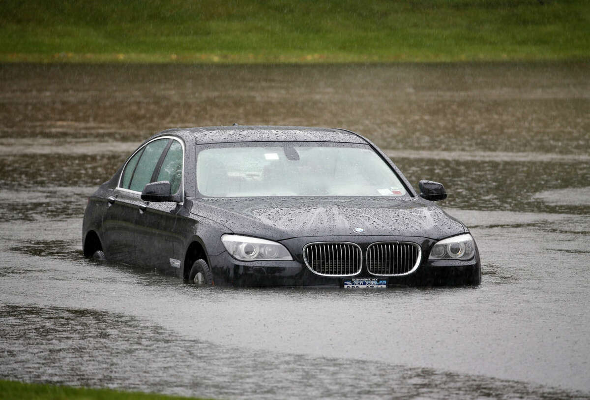 A vehicle is stranded on a flooded driveway leading to a shopping plaza on Wednesday, Sept. 30, 2015, in Guilderland, N.Y. The National Weather Service has issued flood watches for much of the eastern half of upstate New York as a storm dumps more than two inches of rain across the region. (AP Photo/Mike Groll)