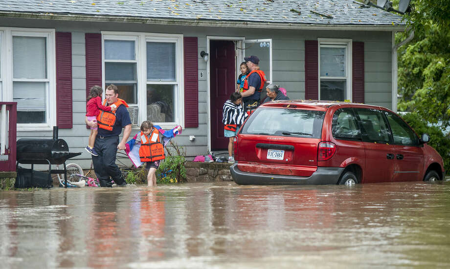Harrisonburg emergency responders help a family evacuate their home as floodwaters block the road in Harrisonburg, Va., on Tuesday, Sept. 29, 2015. The National Weather Service issued flash flood warnings Tuesday in southwest and central Virginia, among other areas, with 2 to 4 inches or rain forecast from the Blue Ridge to the Alleghany Mountains. (Daniel Lin/Daily News-Record via AP) MANDATORY CREDIT
