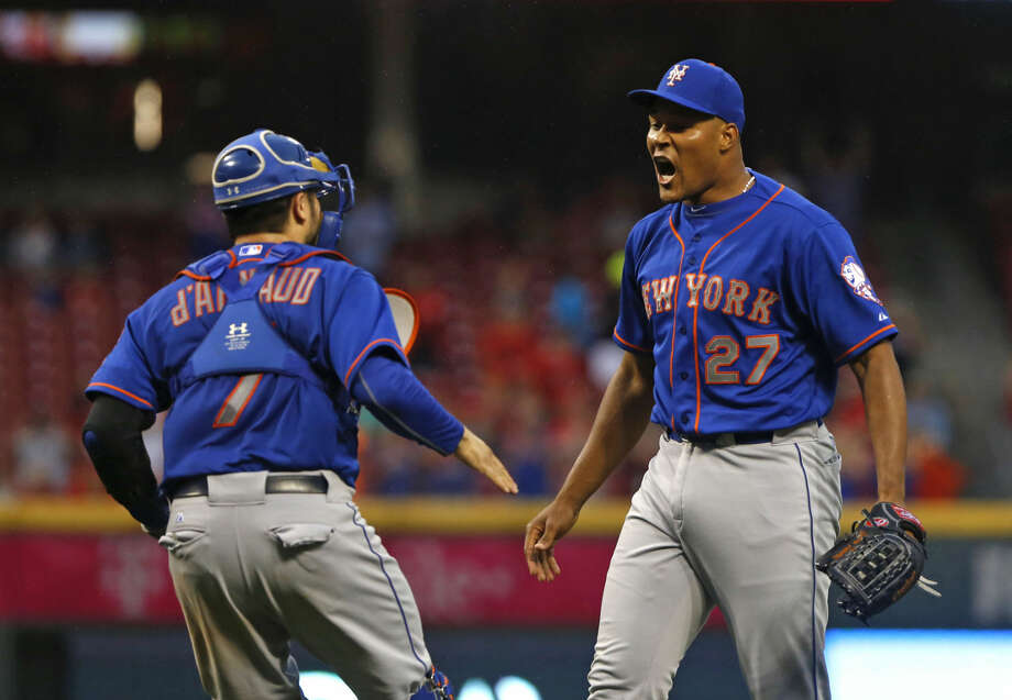 New York Mets relief pitcher Jeurys Familia (27) celebrates with catcher Travis d'Arnaud, left, after the Mets clinched the NL East with a 10-2 win over the Cincinnati Reds in a baseball game, Saturday, Sept. 26, 2015, in Cincinnati. (AP Photo/Aaron Doster)