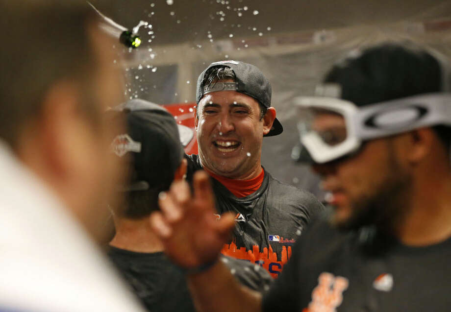 New York Mets pitcher Matt Harvey celebrates with teammates in the clubhouse after the clinching the NL East title following their 10-2 win over the Cincinnati Reds in a baseball game, Saturday, Sept. 26, 2015, in Cincinnati. (AP Photo/Aaron Doster)