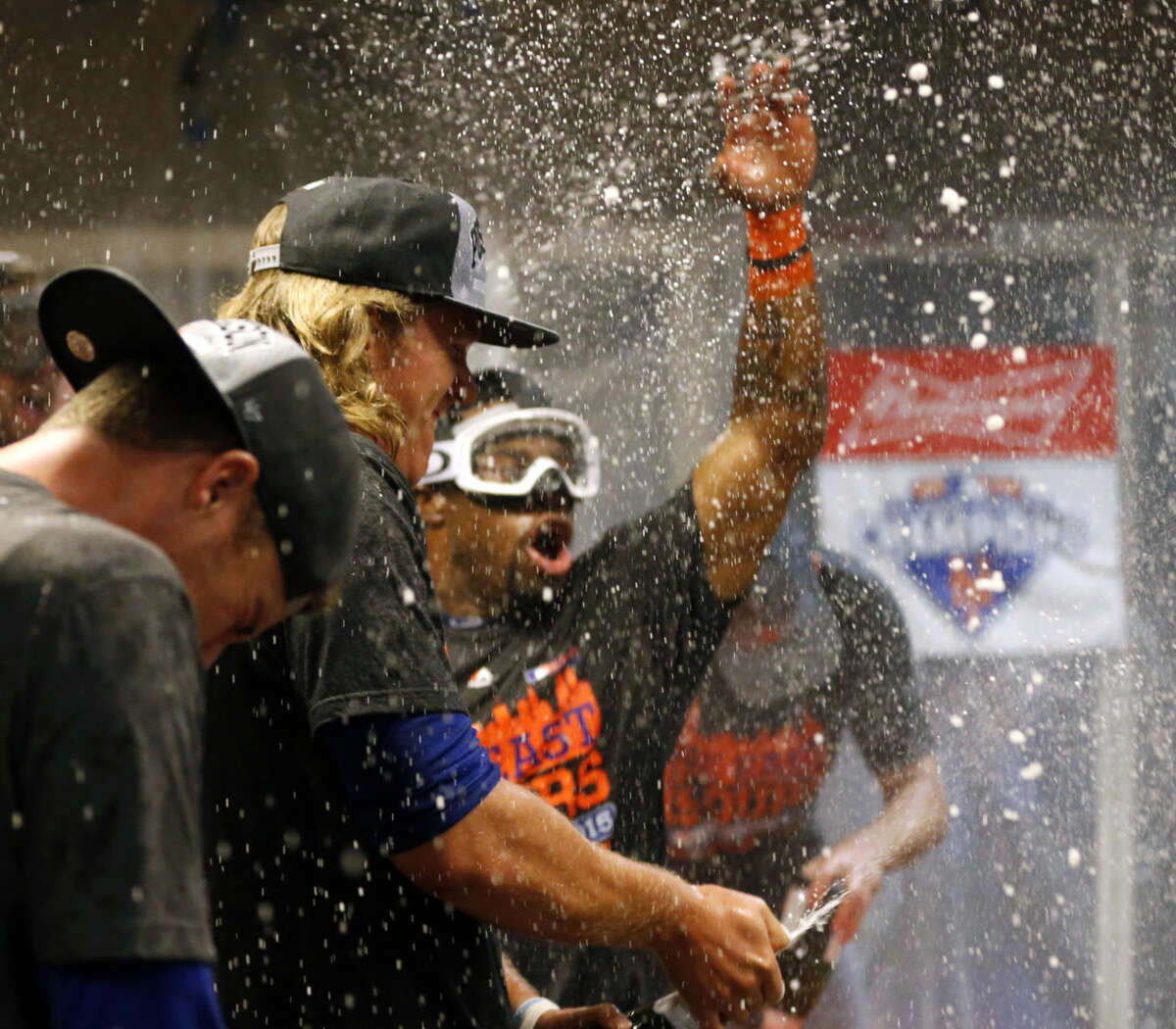 The New York Mets celebrate in the clubhouse after clinching the NL East title following their 10-2 win over the Cincinnati Reds in a baseball game, Saturday, Sept. 26, 2015, in Cincinnati. (AP Photo/Aaron Doster)
