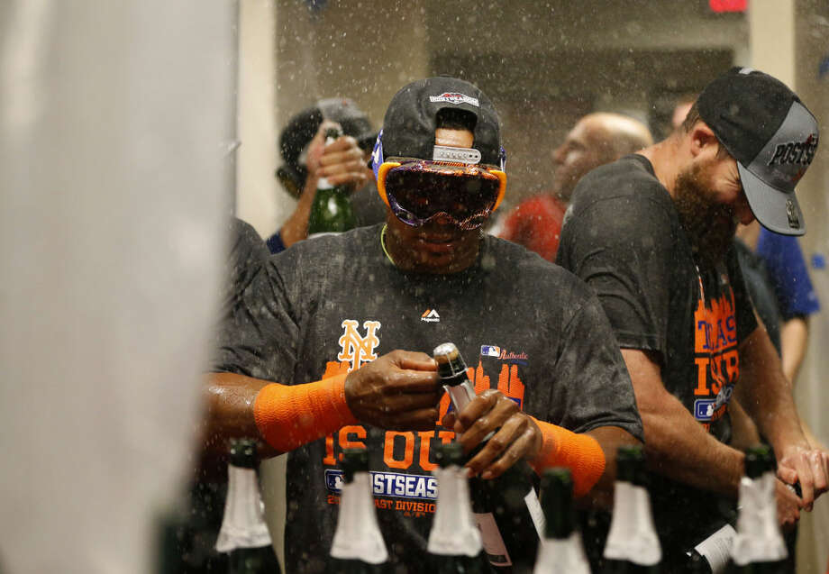 New York Mets' Yoenis Cespedes uncorks champagne as he celebrates with teammates in the clubhouse after clinching the NL East title following their 10-2 win over the Cincinnati Reds in a baseball game, Saturday, Sept. 26, 2015, in Cincinnati. (AP Photo/Aaron Doster)