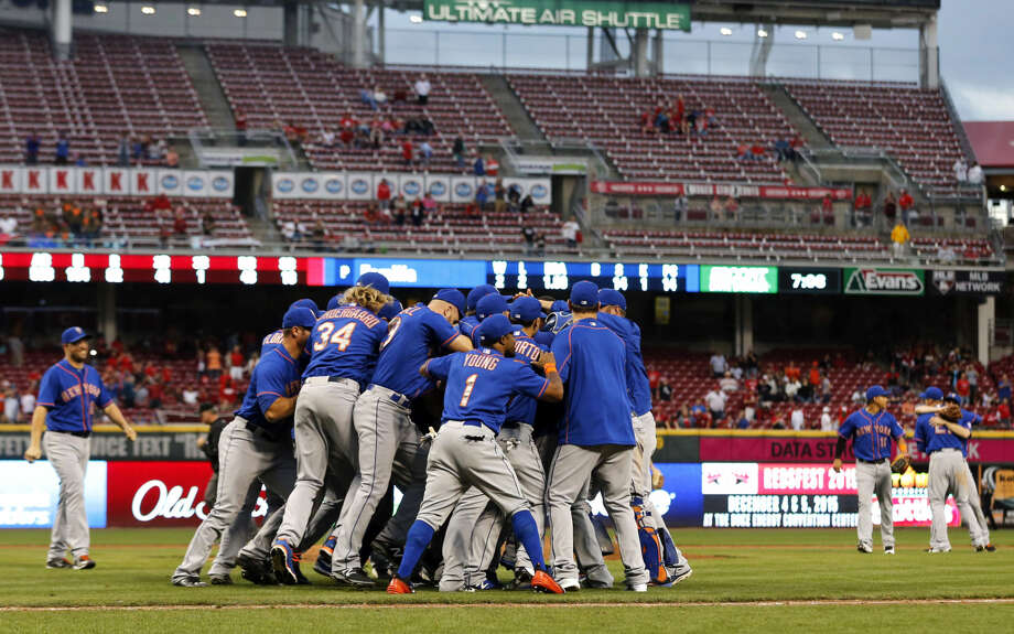 The New York Mets celebrate on the field after clinching the NL East title following their 10-2 win over the Cincinnati Reds, Saturday, Sept. 26, 2015, in Cincinnati. (AP Photo/Aaron Doster)