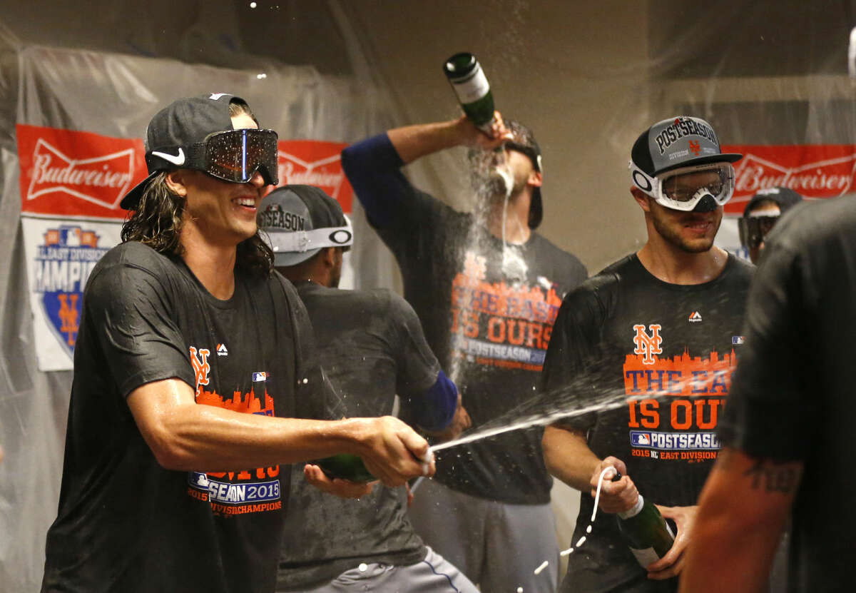New York Mets' Jacob deGrom, left, celebrates in the clubhouse with teammates after clinching the NL East title following their 10-2 win over the Cincinnati Reds in a baseball game, Saturday, Sept. 26, 2015, in Cincinnati. (AP Photo/Aaron Doster)