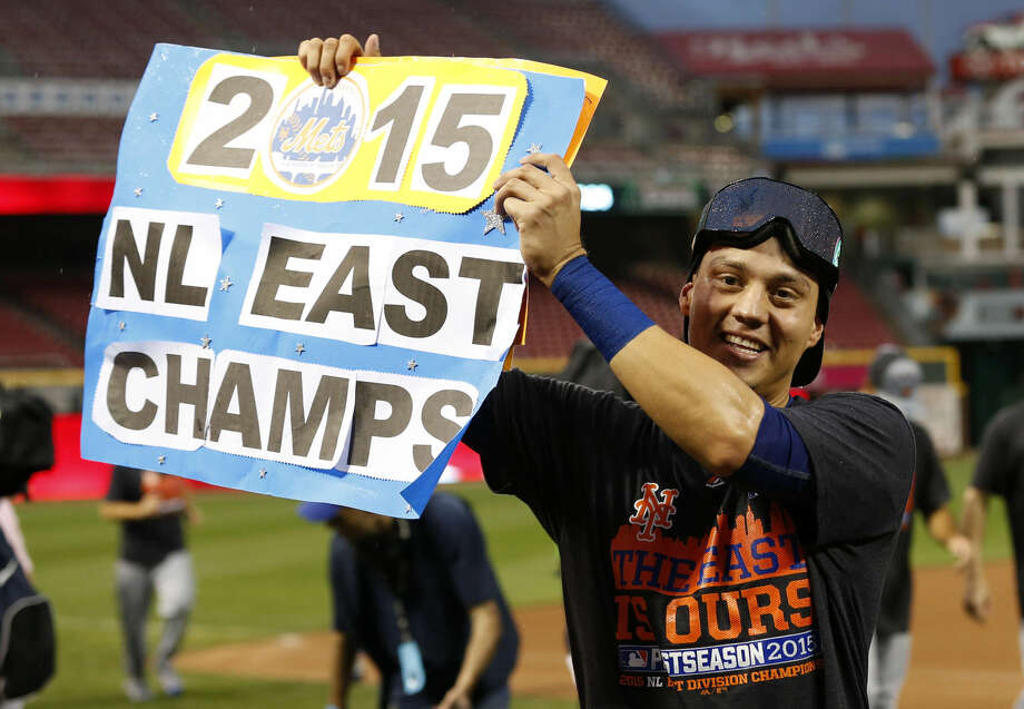 New York Mets' Wilmer Flores holds up a sign as he celebrates after clinching the NL East title following their 10-2 win over the Cincinnati Reds in a baseball game, Saturday, Sept. 26, 2015, in Cincinnati. (AP Photo/Aaron Doster)