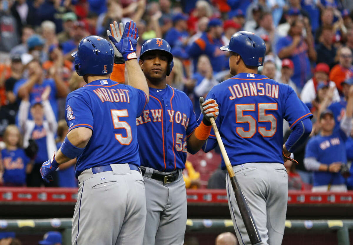 New York Mets' David Wright (5) celebrates with Yoenis Cespedes (52) after hitting a three-run home run in the ninth inning of a baseball game against the Cincinnati Reds, Saturday, Sept. 26, 2015, in Cincinnati. The Mets won 10-2 to clinch the NL East title. (AP Photo/Aaron Doster)