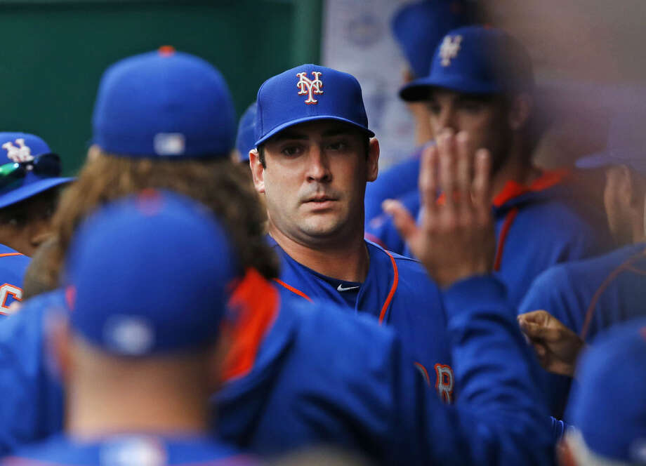 New York Mets starting pitcher Matt Harvey high-fives teammates in the dugout after the sixth inning of a baseball game against the Cincinnati Reds, Saturday, Sept. 26, 2015, in Cincinnati. The Mets won 10-2 and clinched the NL East. (AP Photo/Aaron Doster)