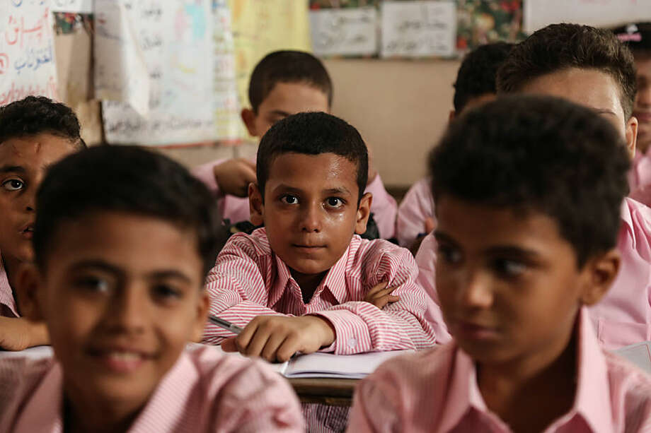 School children attend the first day of classes at the Talaat Harb government primary school, in the popular district of Shubra, Cairo, Egypt, Monday Sept. 28, 2015. Some 19 million Egyptian students began the academic year on Monday as Education minister El-Helali el-Sherbini, told the state-run news agency MENA that the government had repaired 95% of the country's notoriously rundown schools. (AP Photo/Mohamed Elraai)