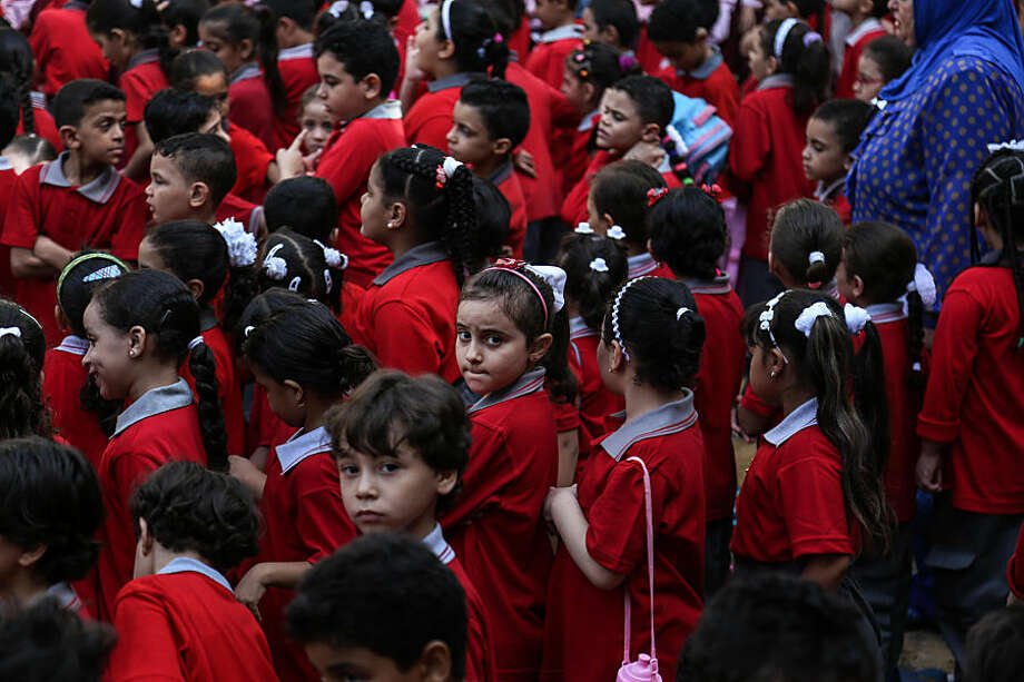 School children line up at the start of the first day of classes, during a visit by the Governor of Cairo Galaal Saeed, at the Talaat Harb government primary school, in the popular district of Shubra, Cairo, Egypt, Monday Sept. 28, 2015. Some 19 million Egyptian students began the academic year on Monday as Education minister el-Helali el-Sherbini, told the state-run news agency MEAN that the government had repaired 95% of the country's notoriously rundown schools. (AP Photo/Mohamed Elraai)