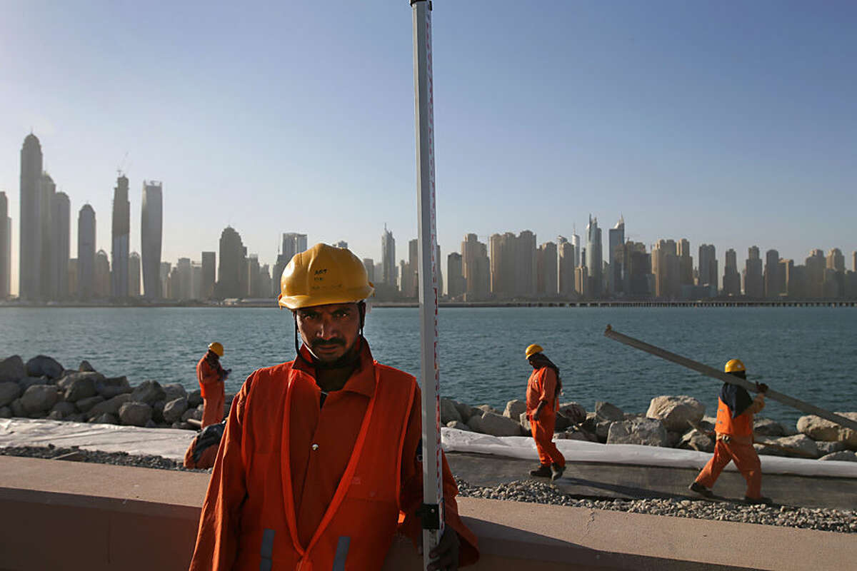 In this Tuesday, Sept. 22, 2015 photo, with the Marina Waterfront skyline in the background, labors work at a construction site at the Palm Jumeirah, in Dubai, United Arab Emirates. The United Arab Emirates is introducing labor reforms that aim to tighten oversight of employment agreements for the millions of temporary migrant workers that comprise the bulk of the country's workforce, a top Emirati official said Tuesday. (AP Photo/Kamran Jebreili)