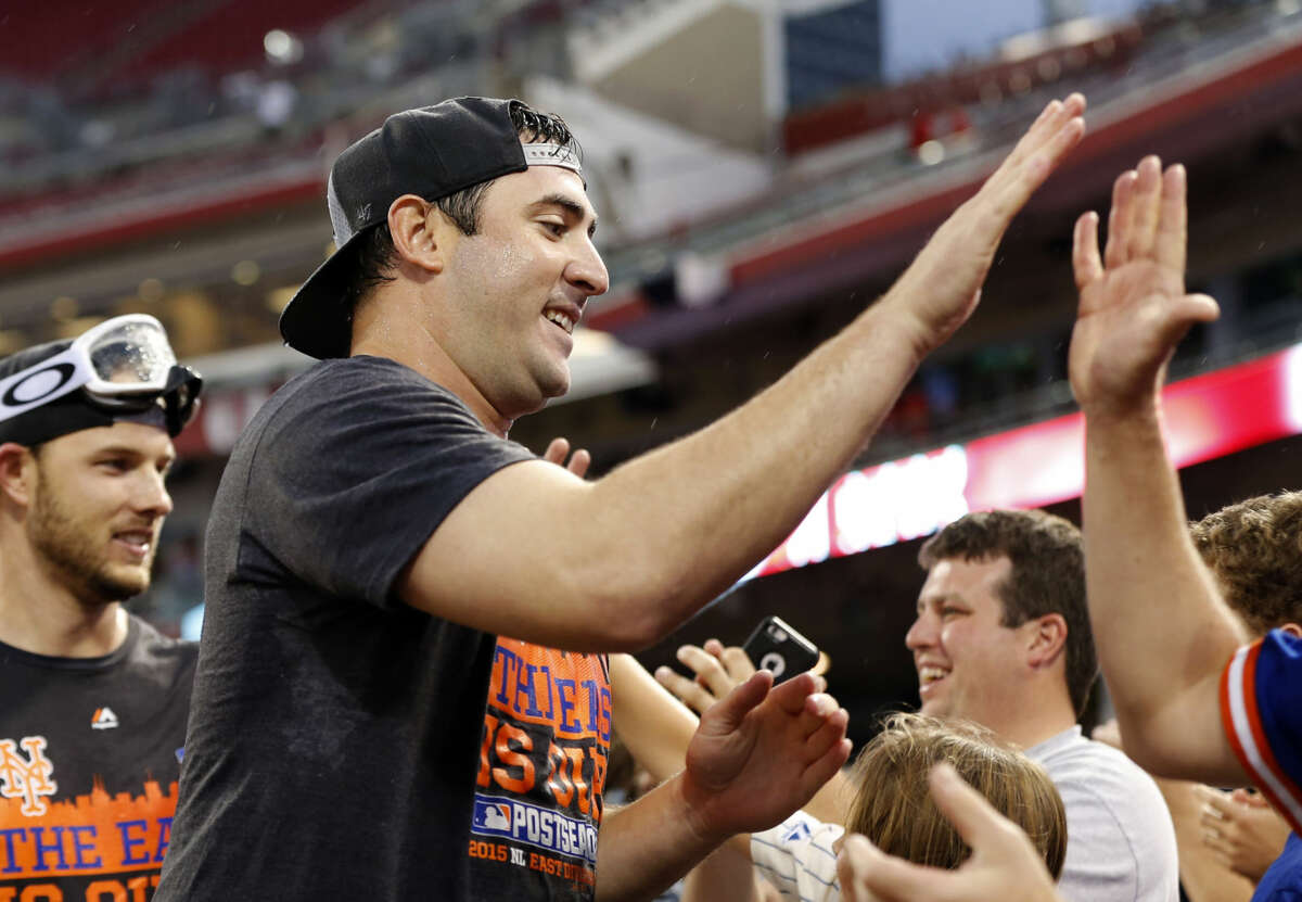 New York Mets' Matt Harvey celebrates with the fans after the clinching the NL East title following their 10-2 win over the Cincinnati Reds, Saturday, Sept. 26, 2015, in Cincinnati. (AP Photo/Aaron Doster)