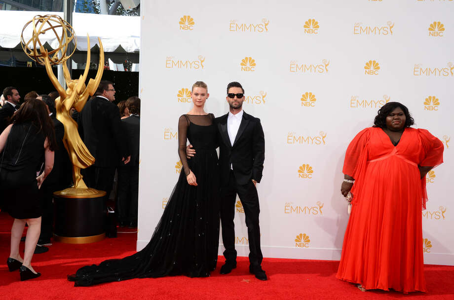 Behati Prinsloo, and from left, Adam Levine and Gabourey Sidibe arrive at the 66th Annual Primetime Emmy Awards at the Nokia Theatre L.A. Live on Monday, Aug. 25, 2014, in Los Angeles. (Photo by Jordan Strauss/Invision/AP)