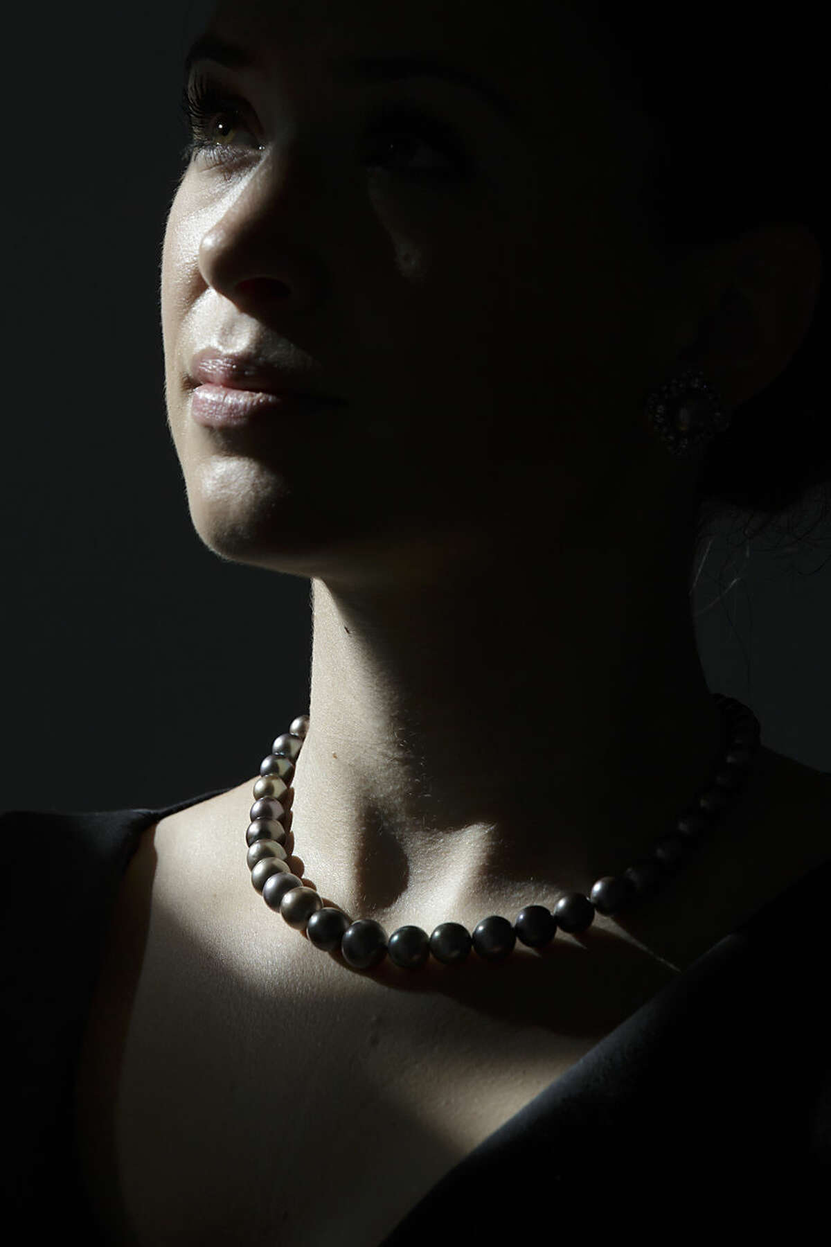 A member of Sotheby's staff poses for pictures with the Cowdray Pearl's, a necklace, strung and mounted by Cartier, of 42 grey saltwater pearls, at the Sotheby's auction house in London, Monday, Sept. 28, 2015. The necklace is due to be auctioned by Sotheby's Hong Kong at the Hong Kong Convention and Exhibition Centre in the Magnificent Jewels and Jadeite Autumn Sale on Oct. 7, and is estimated to fetch up to $7 million (4.6 million pounds) (AP Photo/Tim Ireland)