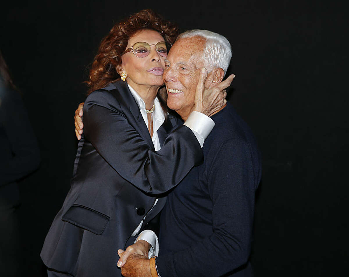 Actress Sophia Loren, left, kisses Italian fashion designer Giorgio Armani at the end of the presentation of his women's Spring-Summer 2016 collection, part of the Milan Fashion Week, unveiled in Milan, Italy, Monday, Sept. 28, 2015. (AP Photo/Luca Bruno)